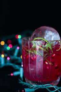 Red cocktail with holiday lights