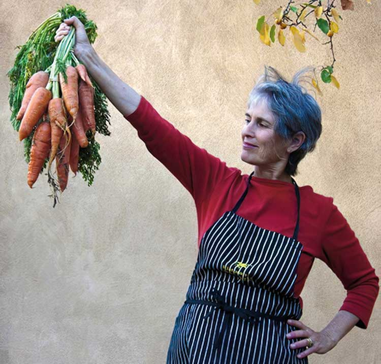 Author Deborah Madison holding a bunch of carrots
